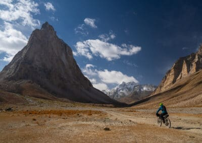 woman wearing warm jacket and green helmet bikes through a desert landscape surrounded by snow-capped mountains