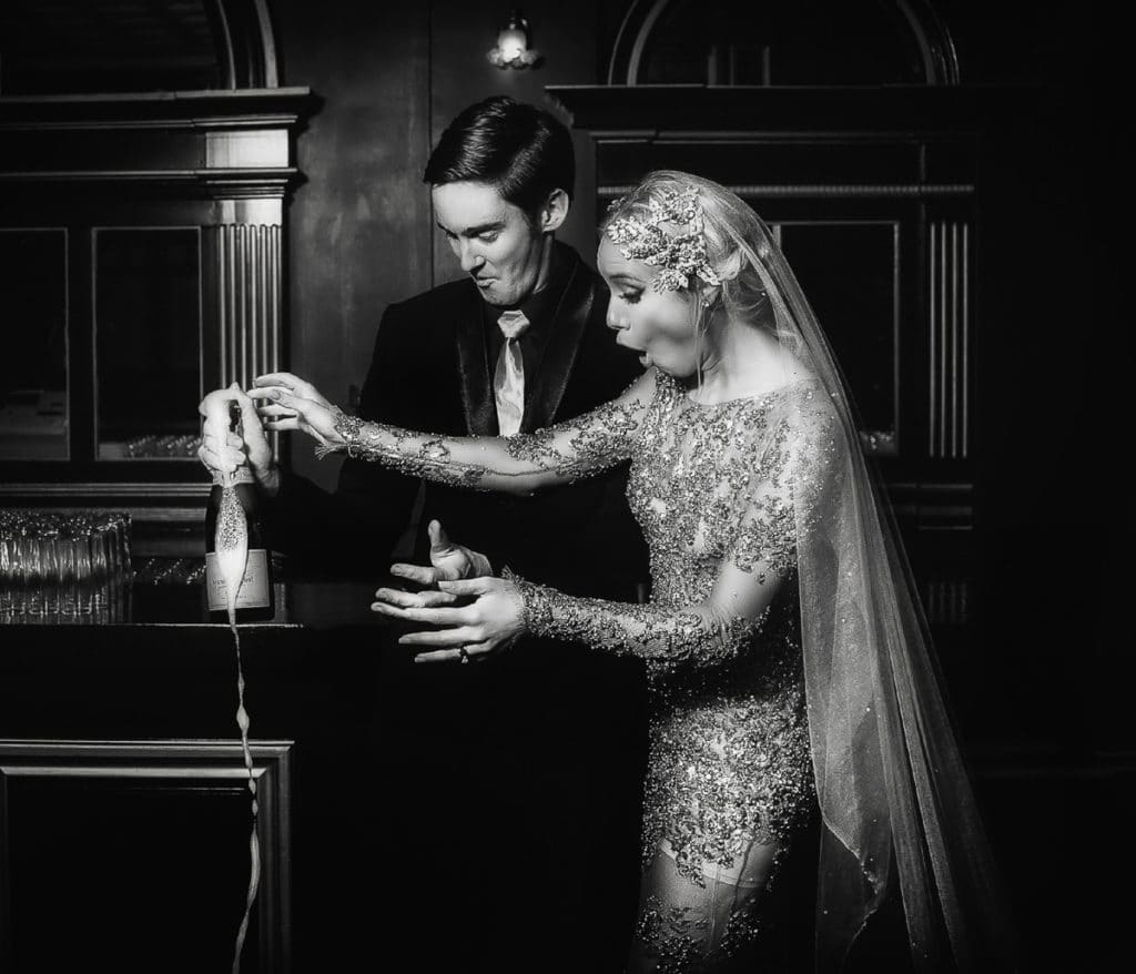 Newly married couple hold a just popped champagne bottle as featured in Conference + Chill Film Photography
