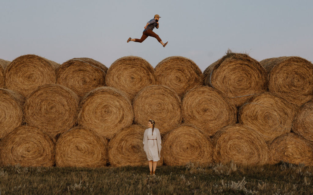Mike of Shari + Mike, hosts of Conference + Chill, jumps on hay bales while Shari stands below