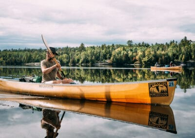 bearded white guy wearing a hat, tshirt and shorts, paddles a canoe on a glass-like lake image by cliford mervil outdoor commercial photographer