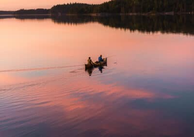 two fisherman fish from a canoe at sunset on a still lake in this image by outdoor commercial photographer cliford mervil