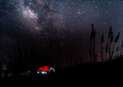 a tent lit up at night under the stars and milky way with a red tent and blue sides and the outlines of grass and trees by cliford mervil conference and chill speaker
