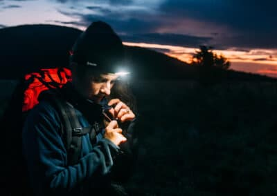 white woman dressed for backpacking at night shines her headlamp on her zipper to adjust it with the sun nearly setting behind her and trees silhouetted in the distance image by conference and chill speaker cliford mervil
