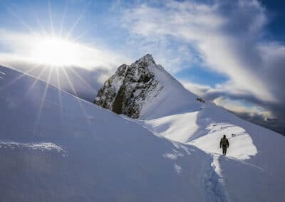 dave brosha walks a path through the mountains on a bluebird day with the sun shining above him image by paul zizka