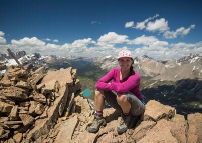 meghan ward, canadian outdoor adventure writer and editor, sits at the top of a cliff in the mountains. image taken by her husband, paul zizka