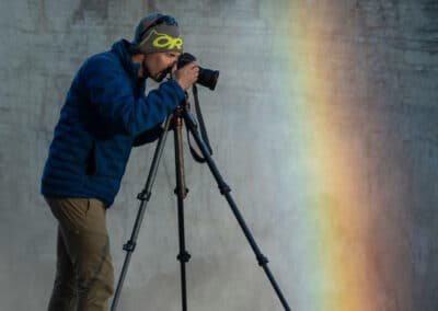 paul zizka stand on the edge of a cliff in a rainbow looking through his camera while shooting on location. image taken by conference and chill speaker dave brosha