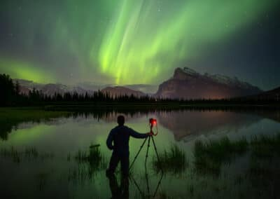Paul Zizka stands silhouetted with hand on camera and tripod under the northern lights of greenland