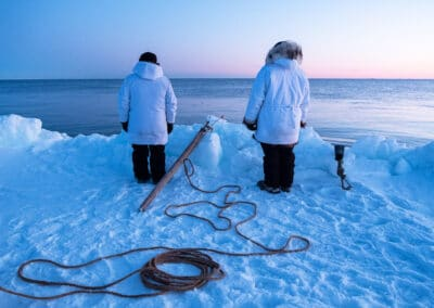 eskimos fish off an iceberg in the arctic while the sun sets in the distance
