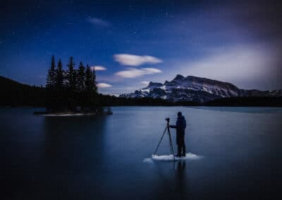 paul zizka stands on froken lake with tripod at night with he and tripod silhouetted, waiting for full dark to shoot