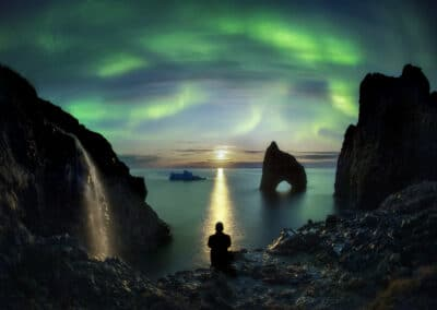 paul zizka, canadian outdoor photographer, stands silhouetted by the northern lights in greenland