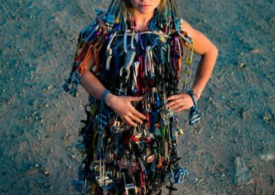 funny photo of a rock climbing woman wearing a dress made of rope and carabiners by irene yee outdoor adventure photographer