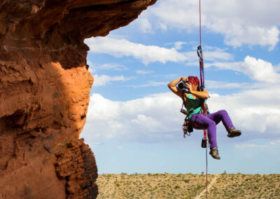 irene yee, rock climbing photographer and conference and chill outdoor adventure edition speaker hangs suspended from a rope while photographing climbers in the Las Vegas desert