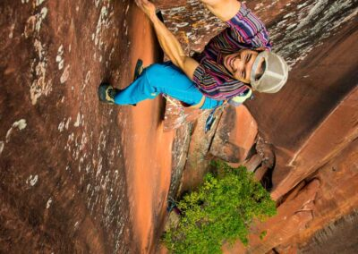 dude with hat backwards climbs the third pitch of elephant riders sheer rockface while smiling up at the photographer irene yee
